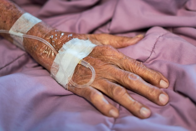 Close up on elder patient's hand with normal saline tube, elder patient receiving a normal saline through the hypodermic syringe (injector).