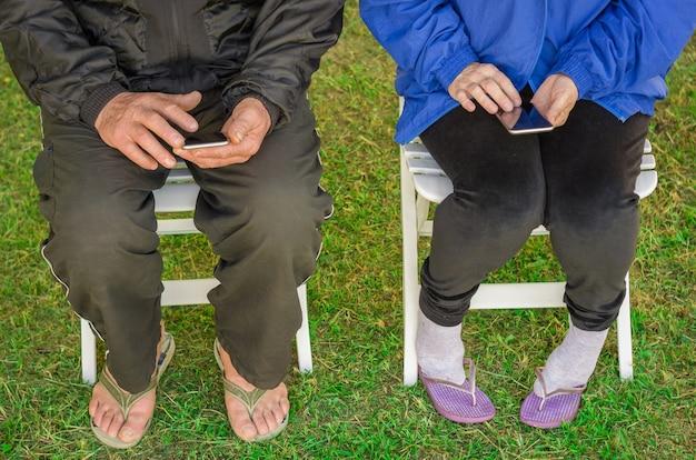 Close up of elderly couple sitting using smartphone
