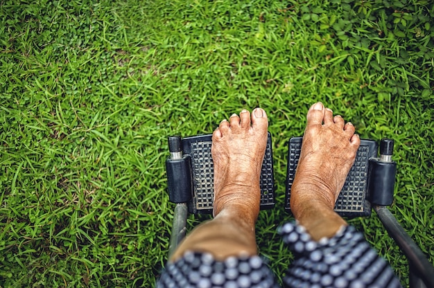 Close up elderly lady feet paresis sitting on wheelchair