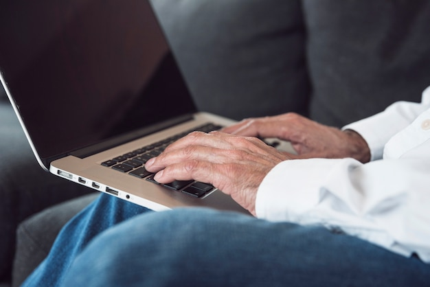 Close-up of an elderly man's hand typing on laptop