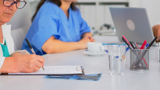 Close up of elderly woman doctor taking notes on clipboard while coworkers discussing in background, writing on laptop during brainstorming. profesional teamworker having medical meeting