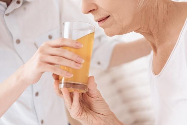 閉じる。高齢者の女性が病院でジュースを飲みます。