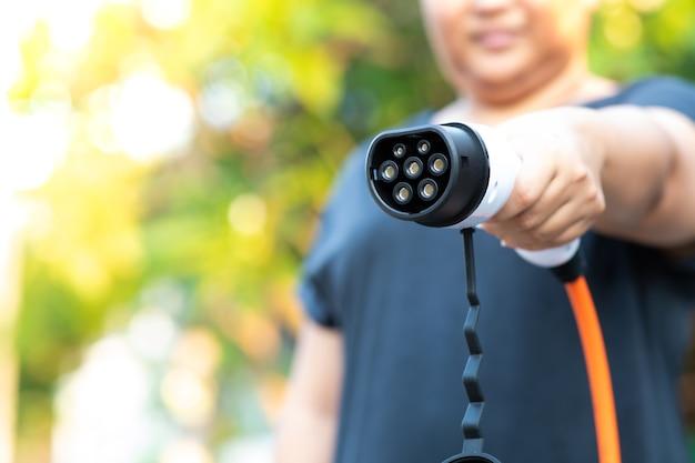 Крупным планом женщина рука вилки электромобиля для подзарядки вилки в гибридном автомобиле дома или зарядной станции.