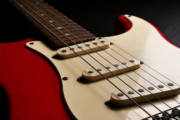 Close up of electric guitar body detail on black background.
