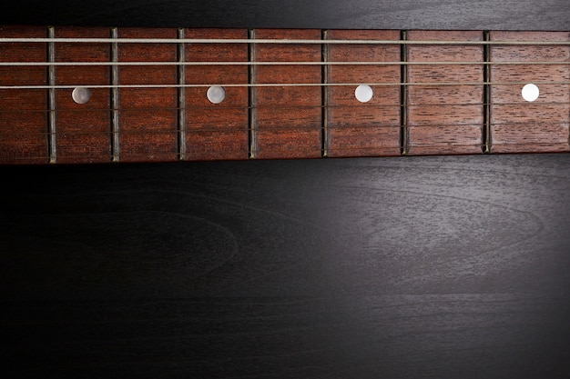 Close up of electric guitar neck fingerboard on a black background. free space for text