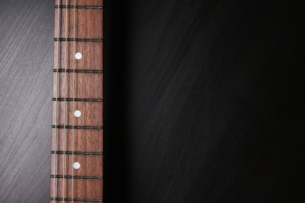 Close up of electric guitar neck fingerboard on a black background.