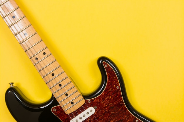 Close-up of electric guitar on yellow background, with copy space