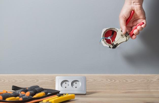 壁のコンセントの電線を剥がすクローズアップ電気技師の手