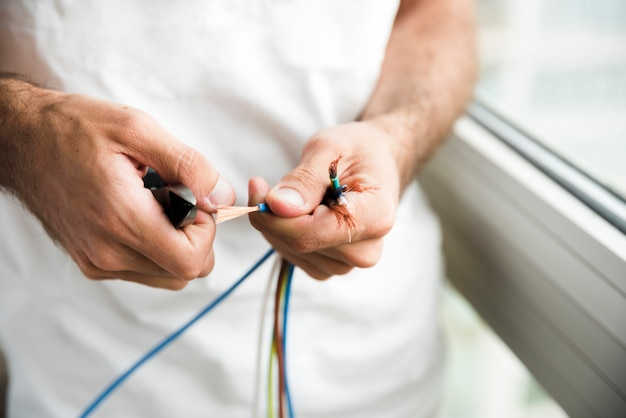 Close-up of a electrician removing plastic coating of cable