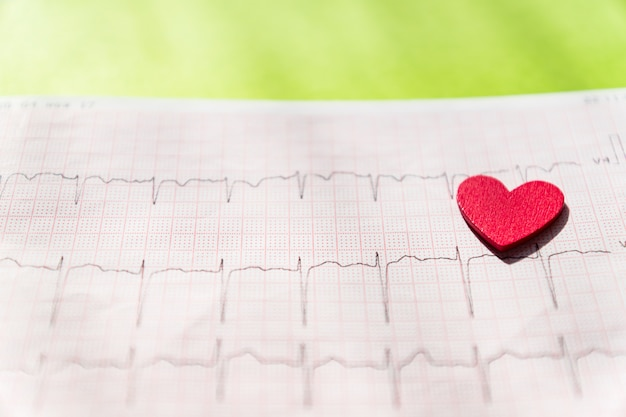 Close up of an electrocardiogram in paper form vith red wooden heart. ecg or ekg paper. medical and healthcare concept.