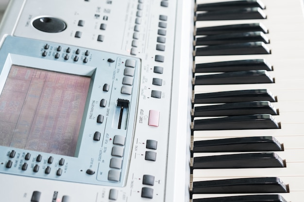 Close-up electronic musical keyboard and piano for playing song.