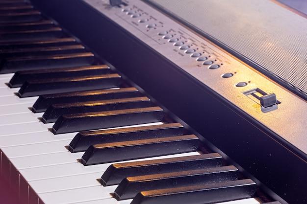 Primo piano di una tastiera di pianoforte elettronica in bella illuminazione.