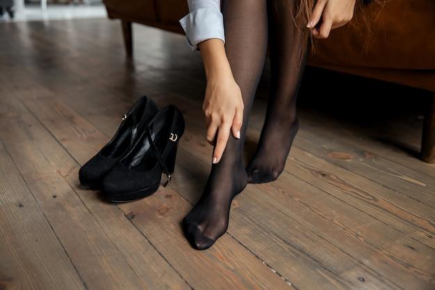 Закройте вверх. элегантная деловая женщина снимает обувь и отдыхает после работы дома. фото высокого качества