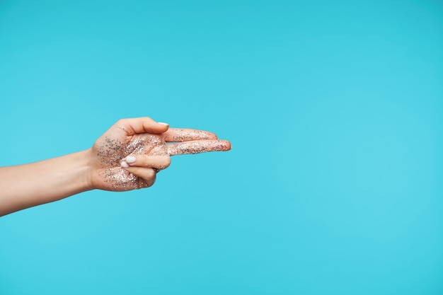 Close up on elegant hand showing palm with glitter while isolated