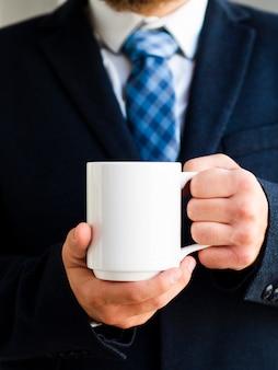 Close-up elegant man holding up mug