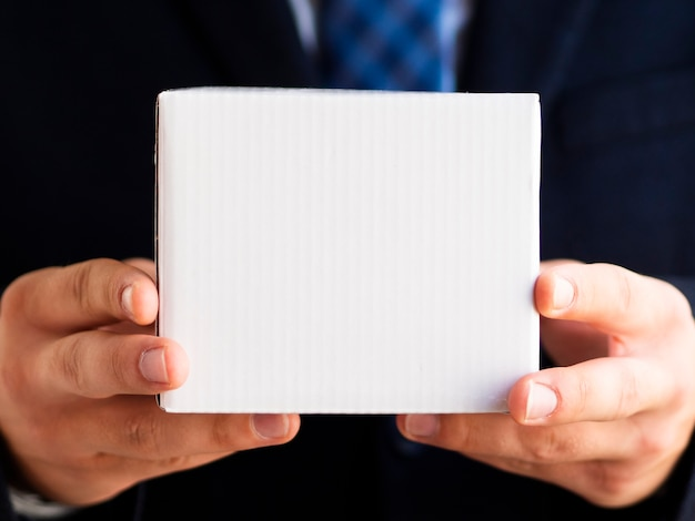 Close-up elegant man holding up small box