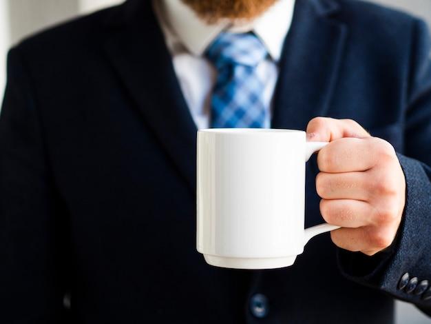 Close-up elegant man holding up white mug
