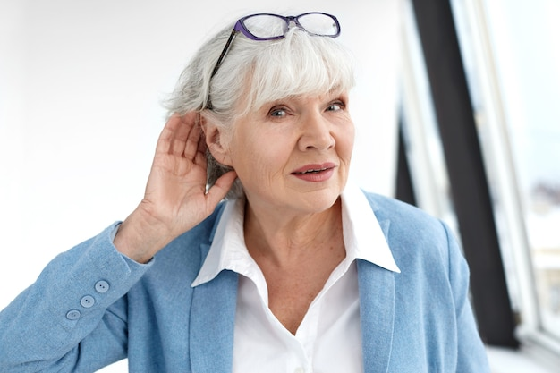 Close up elegant stylish elderly woman in formal suit having hearing problems, holding hand at her ear, trying to hear you, saying: speak louder, please. age, maturity, people and health concept
