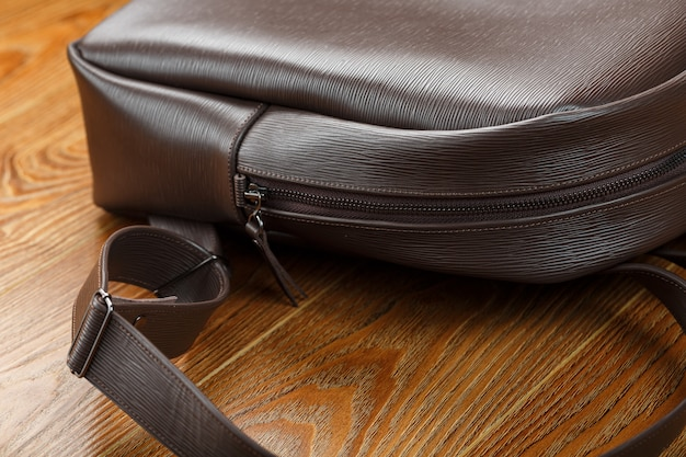Close-up elements and details of the backpack made of brown genuine leather on a wooden table.