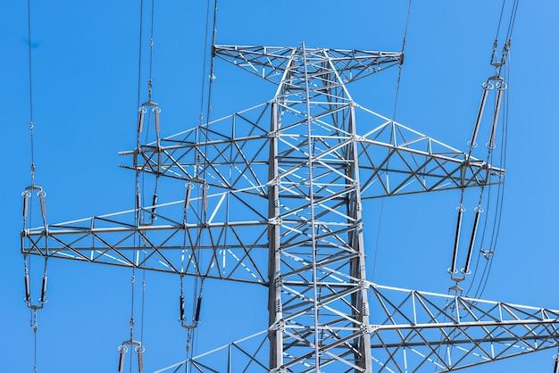 Закройте вверх по электрической башне на голубом небе