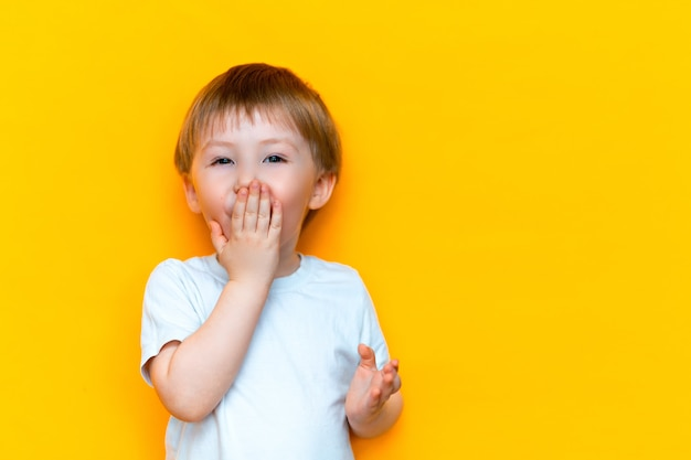 Close up emotional surprised little boy covering mouth