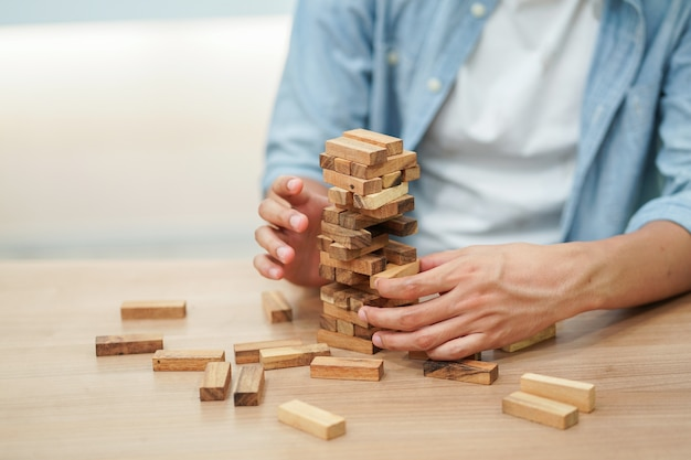 Close up employee man hand holding wooden block for playing jenga game