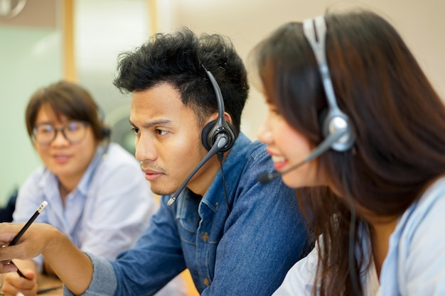 Close up on employee man and team of working call centre hotline at office computer