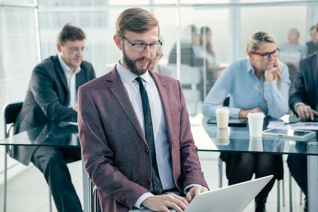 Закройте вверх. сотрудник использует ноутбук на рабочем месте в офисе