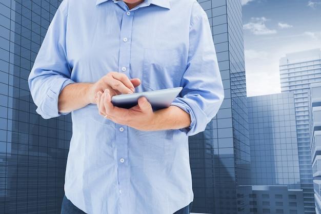 Primo piano di dipendente utilizzando una tavoletta con edifici di sfondo