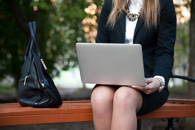 Close-up of employee with laptop on her knees