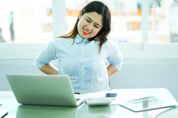 Close up employee woman stretching her back after hard working