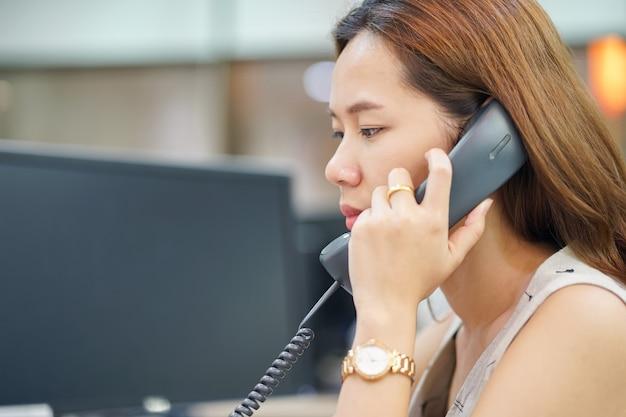 電話で話す従業員の女性を閉じます