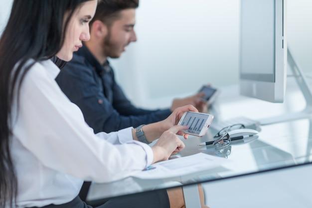 닫기 직원은 가제트를 사용하여 재무 데이터와 함께 작업합니다.사람 및 기술