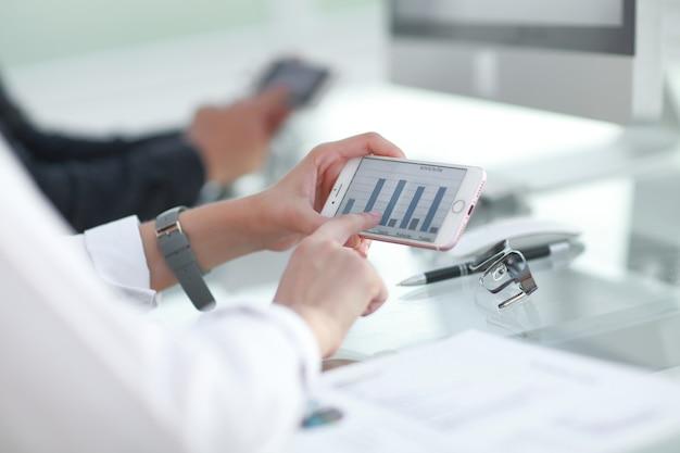 닫기 직원은 스마트폰을 사용하여 재무 데이터를 사용합니다.사람 및 기술
