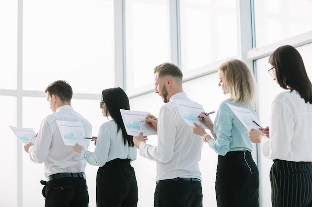 확대. 재무 보고서를 가진 직원들이 줄을 서 있습니다. 비즈니스 개념