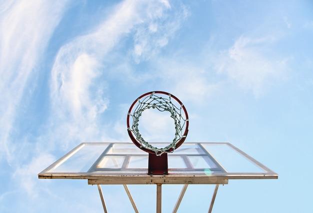 Закройте обруч пустой баскетбольной корзины на открытом воздухе на фоне голубого неба, под низким углом, прямо под