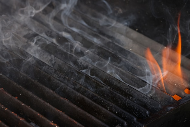 화염과 연기가 있는 빈 주철 금속 바베큐 그릴을 닫습니다