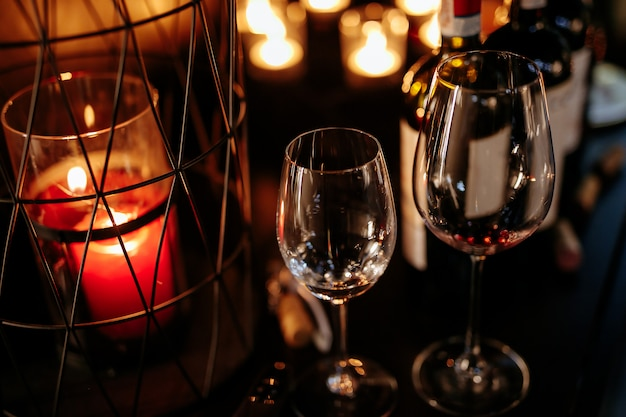 Close up of empty goblets on table decorated with candles