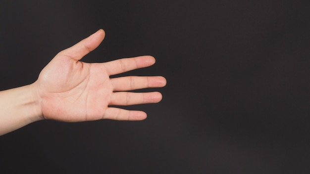 Close up of empty left hand palm and inches apart finger on black background.