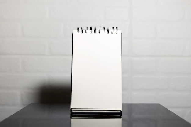 Close-up of empty page of notebook on black glass table