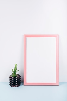 Close-up of a empty photo frame with small potted plant on blue desk