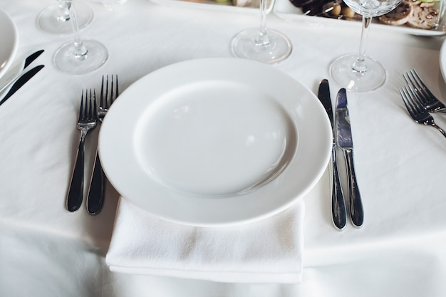 Close-up empty serving white big plate surrounded by knife fork ready to eating food high angle. beautiful tableware on white tablecloth at luxury fashionable restaurant before dinner