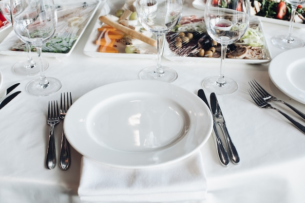 Close-up empty serving white big plate surrounded by knife fork ready to eating food high angle