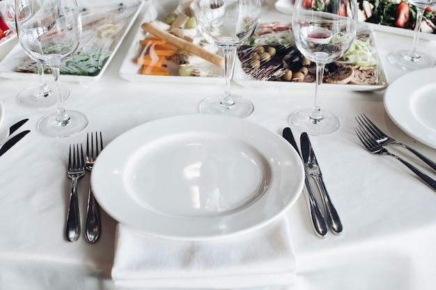クローズアップ空サービングナイフフォークに囲まれた白い大きなプレートは、食品の高角を食べる準備ができて