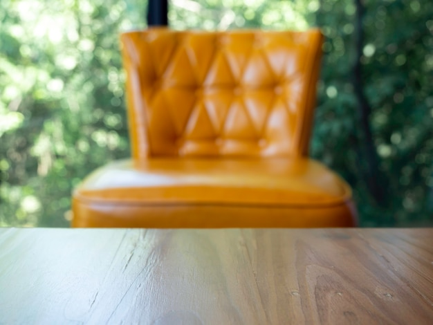 Close-up empty space on wooden table near vintage yellow leather sofa with pins and buttons on green nature background.