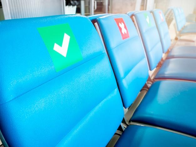社会的な距離のサインとクローズアップ空の待機椅子