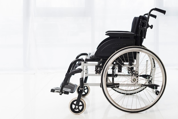Close-up of an empty wheelchair in a room with white curtain