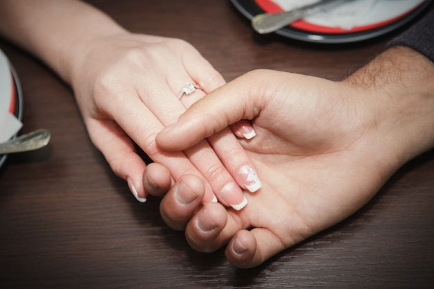Close up of engaged couple holding hands with diamond ring over holidays lights