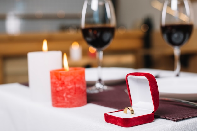 Close-up of engagement ring and burning candles