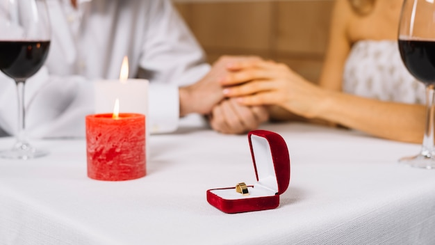 Close-up of engagement ring and candles